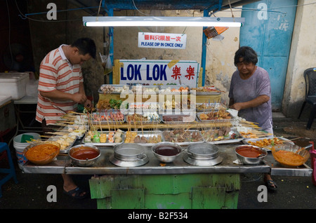 Malaysian street vendor preparing snacks on sticks at a street side food stall in Chinatown, Georgetown, Penang, - Stock Photo