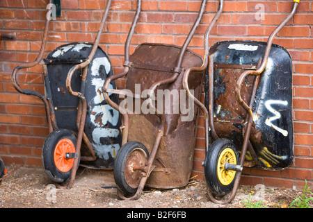 3 wheelbarrows against a wall in an allotment - Stock Photo