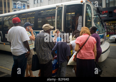 Commuters board a bus in downtown Brooklyn in New York - Stock Photo