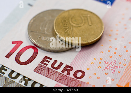 Hungarian Forint coins sit on top of Euro banknotes - Stock Photo