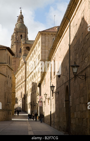 SPAIN Salamanca View of spires of Iglesia San Benito church down narrow cobblestone street lined with buildings - Stock Photo