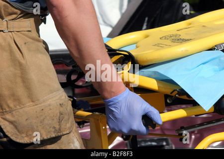 An EMS worker preparing the stetcher for a victim to be loaded after an accident to be transported to the hospital - Stock Photo
