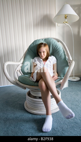 Girl teenager sits in a chair in her living room on vacation and acting silly - Stock Photo