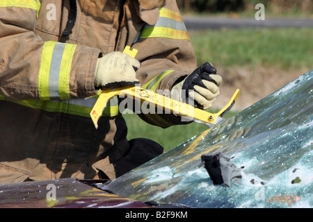 A firefighter using a Glass Master tool to cut out the windshield of a car in an accident during extrication of - Stock Photo