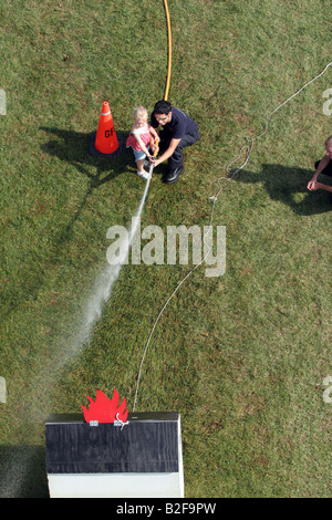A young girl using the water hose to put out the fire on the display house from an aerial view - Stock Photo