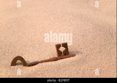 A rusty old key part buried in sand - Stock Photo