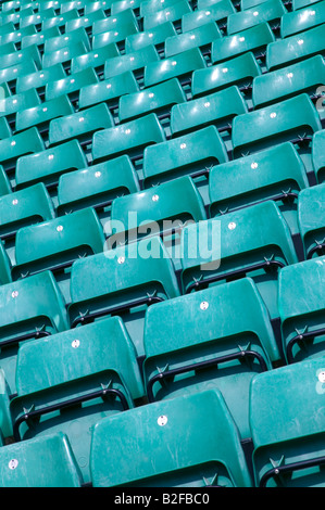 Rows of empty green plastic seats in a sports stadium - Stock Photo