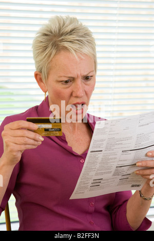 shocked woman reading credit card / bank statement - Stock Photo