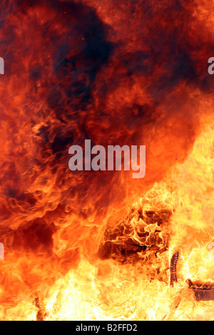 A room on fire with a charred chair in the lower right - Stock Photo