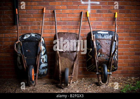 3 wheelbarrows against a wall in an allotment - Stock Photo