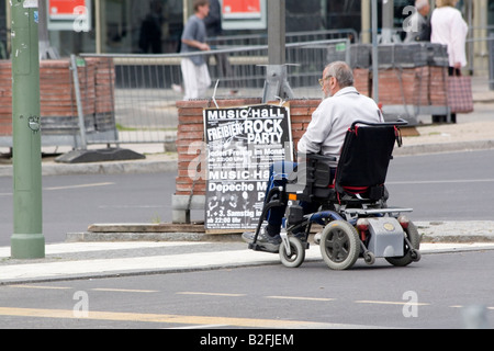Senior man in electric scooter reading poster on street - Stock Photo