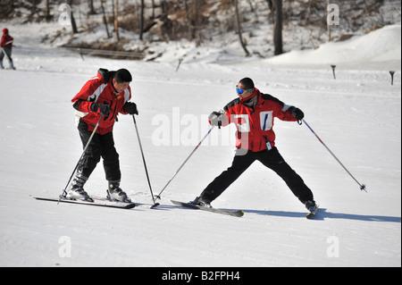 Novice Chinese skier learning from an instructor at Yabuli Ski Resort 200km southeast of Harbin, Heilongjiang Province, - Stock Photo