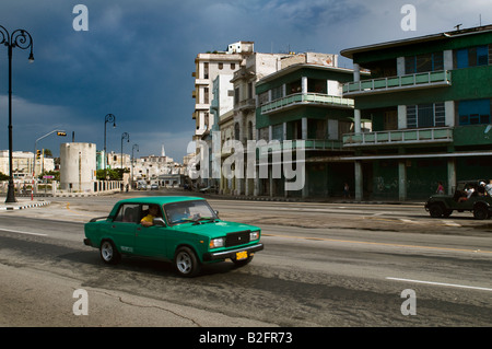 green old 50's style car drives along the malecon in havana - Stock Photo