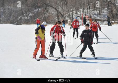 Novice Chinese skiers learning from an instructor at Yabuli Ski Resort 200km southeast of Harbin, Heilongjiang Province, - Stock Photo