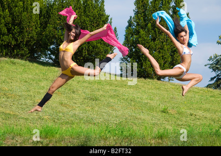 two great girls jumping tougheter in a field with pink and blue scarfe - Stock Photo