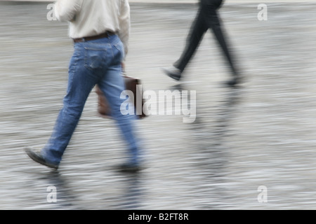 male commuter with briefcase running fast in town - Stock Photo