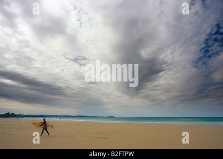 A surfer with surfboard under arm walks from the sea on a beach in Cornwall England with big dramatic skies - Stock Photo