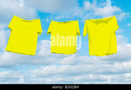 Yellow shirts hanging on a clothes line against a sky full of puffy white clouds - Stock Photo