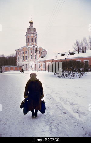 old woman with bags in the snow in st petersburg - Stock Photo