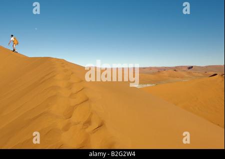 Person climbing a dune - Stock Photo