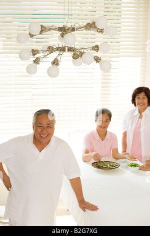 Portrait of a senior man standing with two senior women podding green peas in the background - Stock Photo