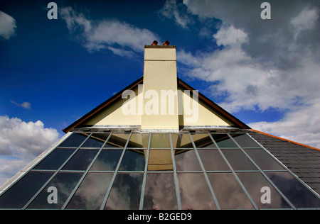 Solar panels on a rooftop in Devon UK reflecting a pitched roof and chimney against a blue sky with clouds. - Stock Photo