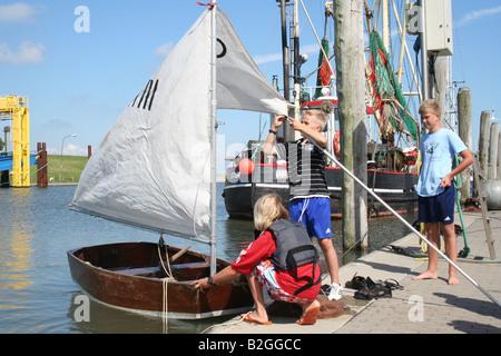 sailing trip boat children  pier dinghy jolle kid landing stage marina mooring - Stock Photo