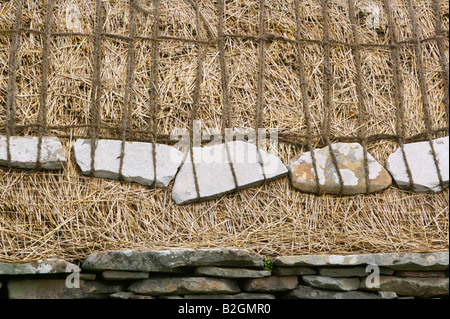 Stone weights and rope to secure the thatch on the roof of the Shetland Crofthouse Museum, Boddam, Shetland Isles, - Stock Photo