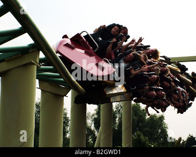 People on a roller coaster ride at theme park - Stock Photo