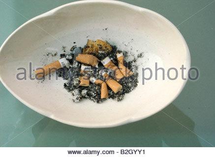 Cigarette Buts in a white  ash tray - Stock Photo