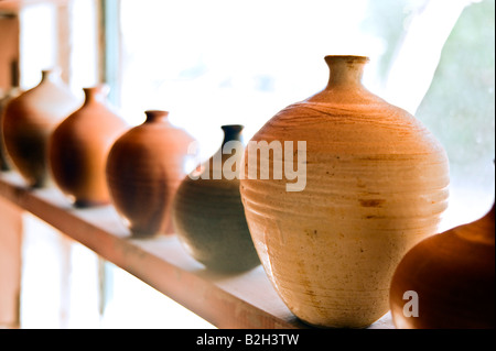 handmade pots vases on a shelf at workshop - Stock Photo