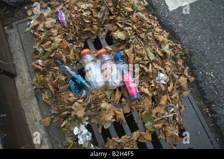 Storm Drain In Street With Trash In Gutter Stock Photo