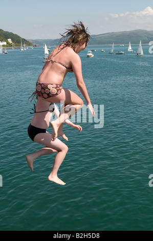 Two teenage girls leaping off the jetty in Aberdyfi into the Dyfi river Estuary summer afternoon, Wales UK - Stock Photo