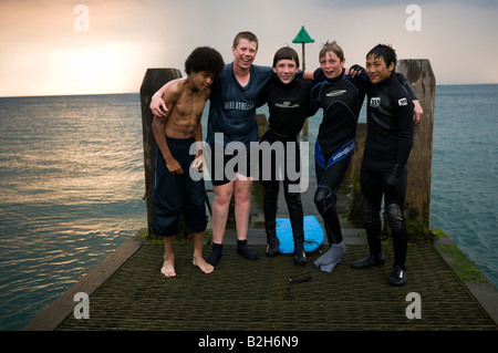 A group of Five teenage boys black chinese and white standing on jetty pier summer evening wearing wet suits Aberystwyth - Stock Photo
