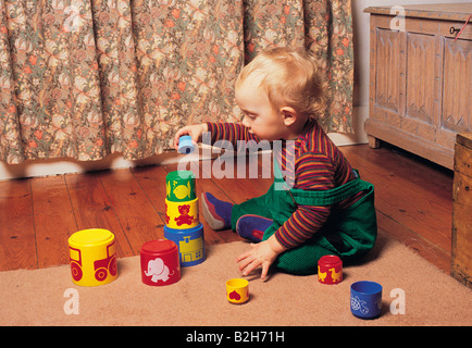 Indoor side view of a little blond haired boy playing with plastic stacking cups. - Stock Photo