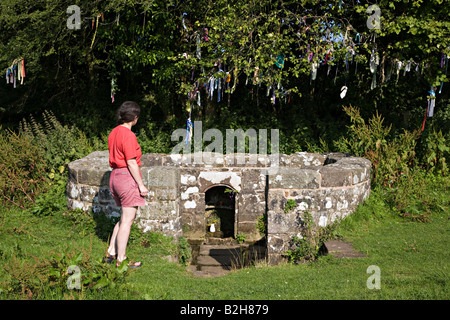 Woman at the 17th century Virtuous Well or St Anne's Well and still dressed with strips of coloured cloth Trellech - Stock Photo