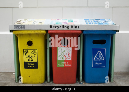 Three colour coded plastic recycling bins for aluminium drink cans, glass and plastic, and paper - Stock Photo