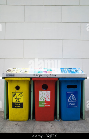 Three colour coded plastic recycling bins for aluminium drink cans, glass and plastic, and paper. - Stock Photo