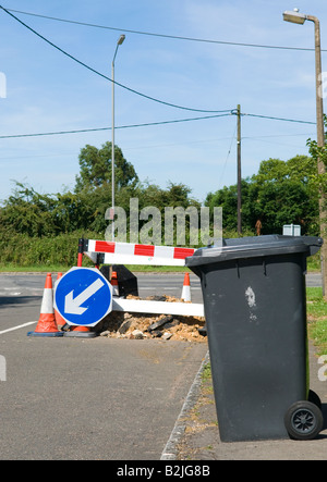 domestic refuse wheelie bin on the pavement awaiting collection with road works in the background - Stock Photo