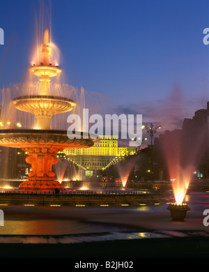 Palace of Parliament seen through fountain on Piata Uniri at night, Bucharest, Romania - Stock Photo
