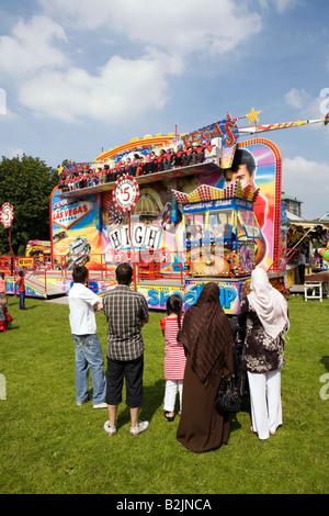 UK England Manchester Platt Fields Mega Mela Asian cultural event people watching funfair ride - Stock Photo