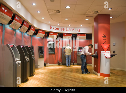 People using automated self service machines at a branch of HSBC bank - Stock Photo