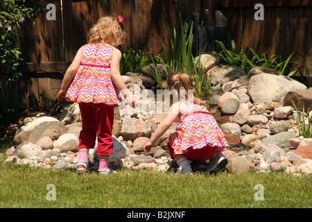 Two twin girls playing next to a pond in the backyard during the summer - Stock Photo