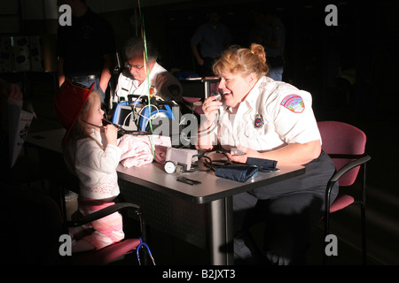 An EMT playing with a young girl while she is listening to the stethoscope - Stock Photo