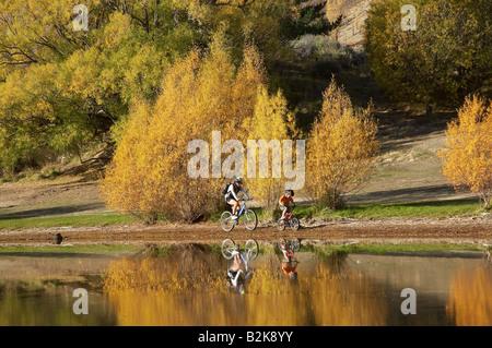Mountain Bikers and Autumn Colours Bannockburn Inlet Lake Dunstan Central Otago South Island New Zealand - Stock Photo