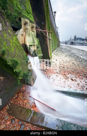Sewage overflow outlet into the river Thames, London city, England, UK. - Stock Photo