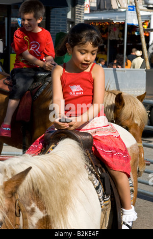 Girl on a pony ride at a festival - Stock Photo