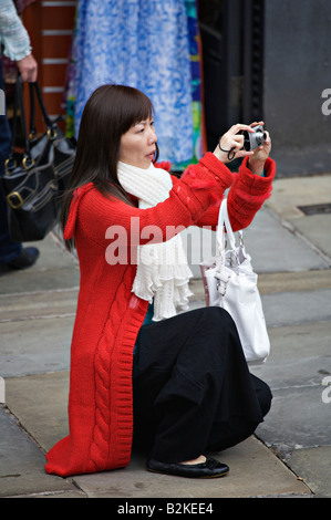 Tourist kneeling to take a photograph in Chester England UK - Stock Photo