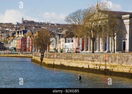 Man in a kneeling canoe making his way up the River Lee in the centre of  Cork City, Ireland - Stock Photo
