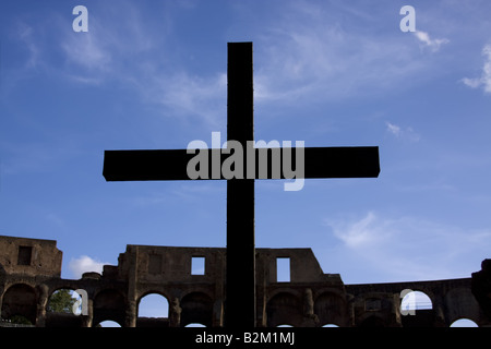 Silhouette of cross over blue sky in colosseum - Stock Photo